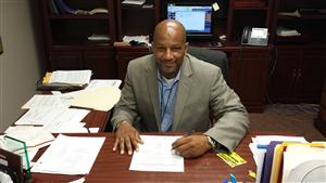 Picture of principal Portee at his desk